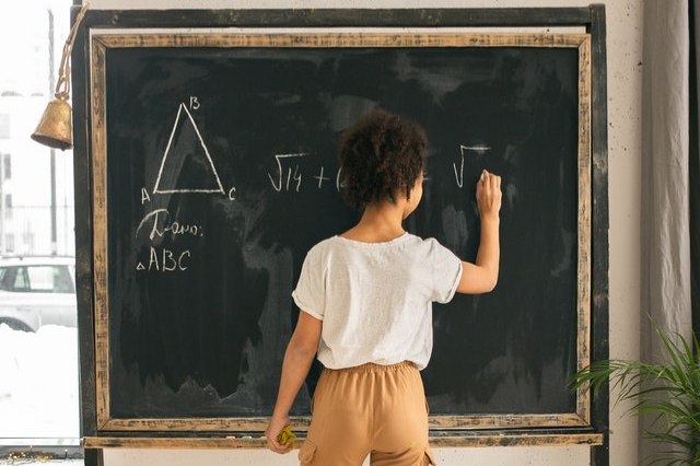 Girl at chalkboard focusing on math equation